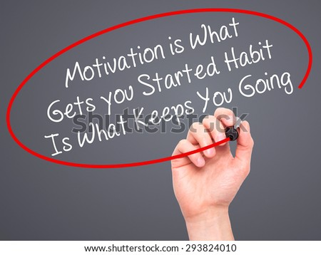 Man Hand writing Motivation is What Gets you Started Habit Is What Keeps You Going with black marker on visual screen. Isolated on nature. grey, technology, internet concept. Stock Photo