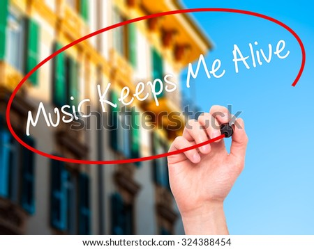 Man Hand writing Music Keeps Me Alive with black marker on visual screen. Isolated on city. Business, technology, internet concept. Stock Photo - stock photo