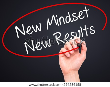 Man Hand writing New Mindset New Results with black marker on visual screen. Isolated on black. Business, technology, internet concept. Stock Photo
