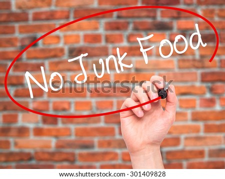 Man Hand writing No Junk Food with black marker on visual screen. Isolated on bricks. Business, technology, internet concept. Stock Photo - stock photo