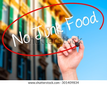 Man Hand writing No Junk Food with black marker on visual screen. Isolated on city. Business, technology, internet concept. Stock Photo - stock photo