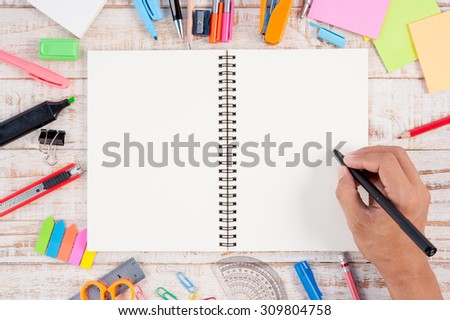 Man hand writing  Notebook paper and school or office tools on vintage wood table for text and background.copy space - stock photo