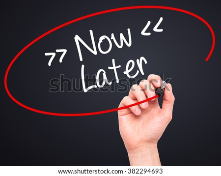 Man Hand writing Now/Later with black marker on visual screen. Isolated on background. Business, technology, internet concept. Stock Photo