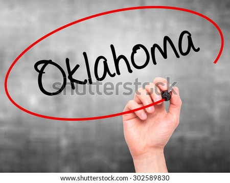 Man Hand writing Oklahoma with black marker on visual screen. Isolated on grey. Business, technology, internet concept.  - stock photo