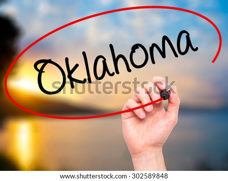 Man Hand writing Oklahoma with black marker on visual screen. Isolated on nature. Business, technology, internet concept.  - stock photo