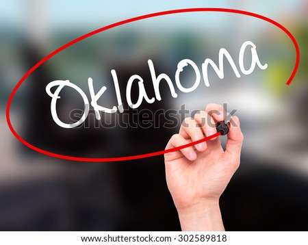 Man Hand writing Oklahoma with black marker on visual screen. Isolated on office. Business, technology, internet concept.  - stock photo