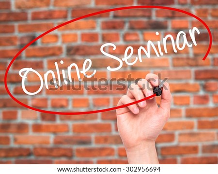 Man Hand writing Online Seminar with black marker on visual screen. Isolated on bricks. Business, technology, internet concept. Stock Photo - stock photo