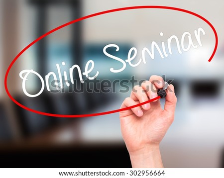 Man Hand writing Online Seminar with black marker on visual screen. Isolated on office. Business, technology, internet concept. Stock Photo - stock photo