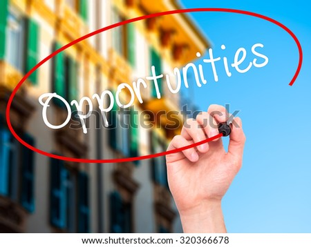 Man Hand writing Opportunities  with black marker on visual screen. Isolated on city. Business, technology, internet concept. - stock photo