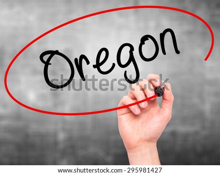 Man Hand writing Oregon with black marker on visual screen. Isolated on grey. Business, technology, internet concept. Stock Photo