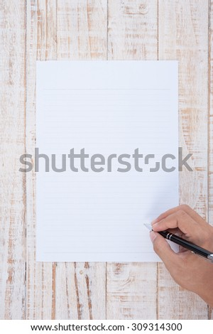 Man hand writing Paper  on wood table for text and background.copy space - stock photo