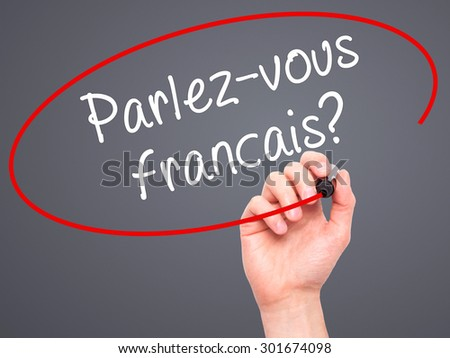 Man Hand writing Parlez-vous français? (Do You Speak French? In French) with black marker on visual screen. Isolated on grey. Business, technology, internet concept. Stock Photo
