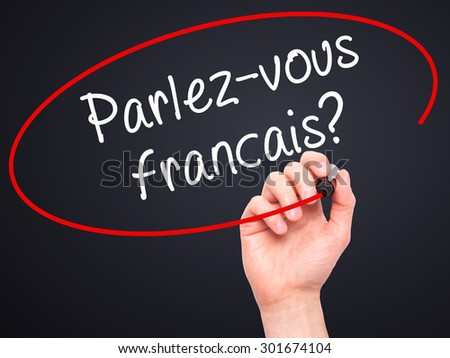 Man Hand writing Parlez-vous français? (Do You Speak French? In French) with black marker on visual screen. Isolated on black. Business, technology, internet concept. Stock Photo