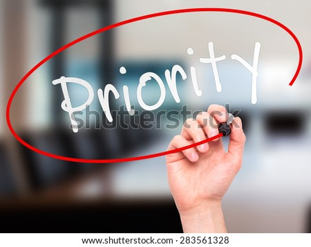 Man Hand writing Priority with marker on transparent wipe board. Isolated on office. Business, internet, technology concept. Stock Photo - stock photo