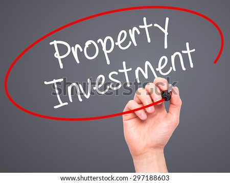 Man Hand writing Property Investment with black marker on visual screen. Isolated on grey. Business, technology, internet concept. Stock Photo