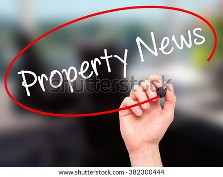 Man Hand writing Property News with black marker on visual screen. Isolated on background. Business, technology, internet concept. Stock Photo - stock photo