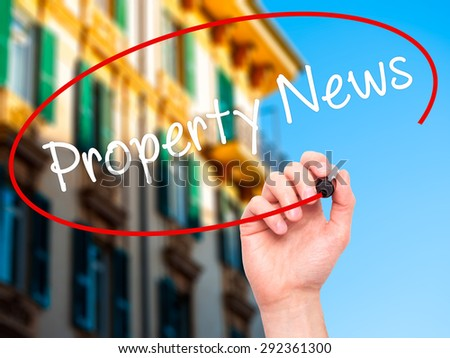Man Hand writing Property News with black marker on visual screen. Isolated on city. Business, technology, internet concept. Stock Image - stock photo