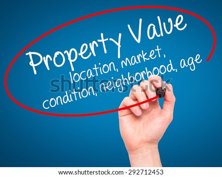 Man Hand writing Property Value - location, market, condition, neighborhood, age with black marker on visual screen. Isolated on blue. Business, technology, internet concept. Stock Image