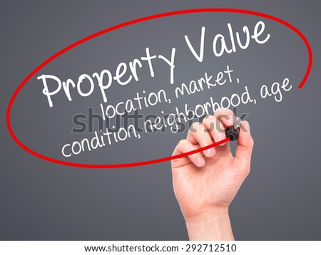 Man Hand writing Property Value - location, market, condition, neighborhood, age with black marker on visual screen. Isolated on grey. Business, technology, internet concept. Stock Image