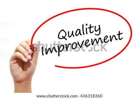 Man Hand writing Quality Improvement with marker on transparent wipe board. Business, internet, technology concept. - stock photo