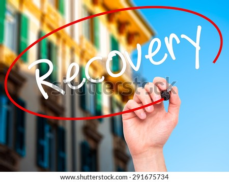 Man Hand writing  Recovery  with black marker on visual screen. Isolated on city. Life, technology, internet concept. Stock Image - stock photo