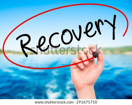 Man Hand writing  Recovery  with black marker on visual screen. Isolated on nature. Life, technology, internet concept. Stock Image - stock photo