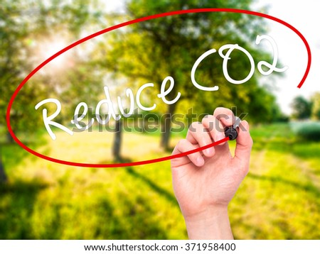 Man Hand writing Reduce CO2 with black marker on visual screen. Isolated on background. Business, technology, internet concept. Stock Photo - stock photo