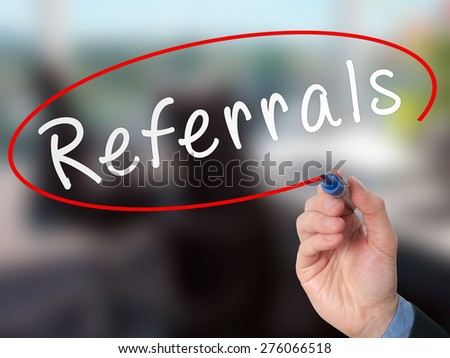 Man Hand writing Referrals with marker on virtual screen. Business, technology, internet concept. Stock Photo
