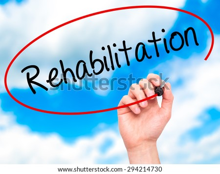 Man Hand writing Rehabilitation with black marker on visual screen. Isolated on sky. Business, technology, internet concept. Stock Photo - stock photo