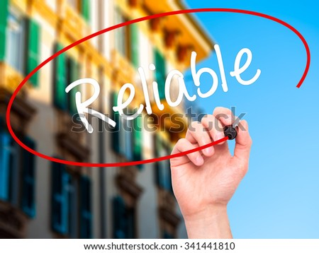Man Hand writing Reliable with black marker on visual screen. Isolated on city. Business, technology, internet concept. Stock Photo - stock photo