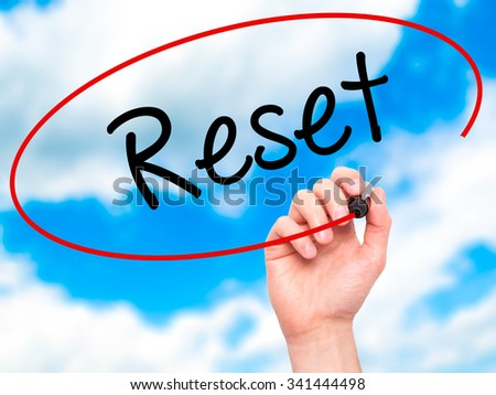 Man Hand writing Reset with black marker on visual screen. Isolated on sky. Business, technology, internet concept. Stock Photo - stock photo