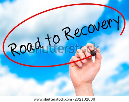 Man Hand writing Road to Recovery with black marker on visual screen. Isolated on sky. Business, technology, internet concept. Stock Image - stock photo