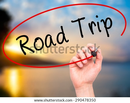 Man Hand writing Road Trip with black marker on visual screen. Isolated on nature. Travel, technology, internet concept. Stock Image - stock photo