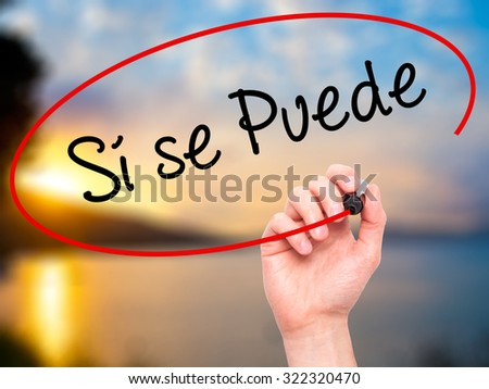 Man Hand writing S� se puede( Yes, it is possible in spanish) with black marker on visual screen. Isolated on nature. Business, technology, internet concept. Stock Photo - stock photo