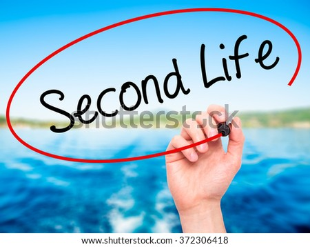 Man Hand writing Second Life with black marker on visual screen. Isolated on background. Business, technology, internet concept. Stock Photo - stock photo