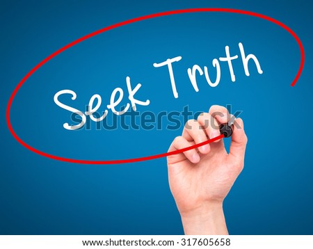Man Hand writing Seek Truth with black marker on visual screen. Isolated on blue. Business, technology, internet concept. - stock photo
