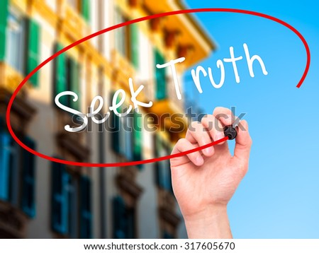 Man Hand writing Seek Truth with black marker on visual screen. Isolated on city. Business, technology, internet concept. - stock photo