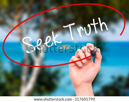 Man Hand writing Seek Truth with black marker on visual screen. Isolated on nature. Business, technology, internet concept. - stock photo