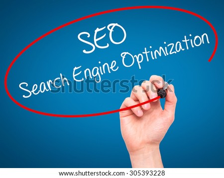 Man Hand writing SEO Search Engine Optimization with black marker on visual screen. Isolated on blue. Business, technology, internet concept. Stock Photo - stock photo