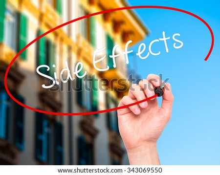 Man Hand writing Side Effects with black marker on visual screen. Isolated on city. Business, technology, internet concept. Stock Photo - stock photo