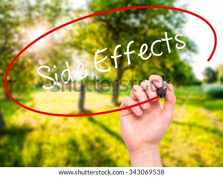 Man Hand writing Side Effects with black marker on visual screen. Isolated on nature. Business, technology, internet concept. Stock Photo - stock photo