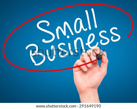 Man Hand writing Small Business with black marker on visual screen. Isolated on blue. Business, technology, internet concept. Stock Image