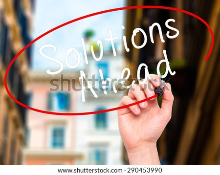 Man Hand writing Solutions Ahead with black marker on visual screen. Isolated on city. Learn, technology, internet concept. Stock Image - stock photo