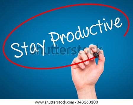 Man Hand writing Stay Productive with black marker on visual screen. Isolated on blue. Business, technology, internet concept. Stock Photo - stock photo