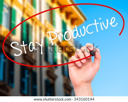 Man Hand writing Stay Productive with black marker on visual screen. Isolated on city. Business, technology, internet concept. Stock Photo - stock photo