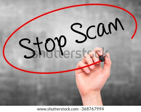 Man Hand writing Stop Scam with black marker on visual screen. Isolated on background. Business, technology, internet concept. Stock Photo