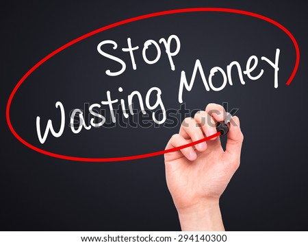 Man Hand writing Stop Wasting Money with black marker on visual screen. Isolated on black. Business, technology, internet concept. Stock Photo - stock photo