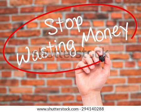 Man Hand writing Stop Wasting Money with black marker on visual screen. Isolated on bricks. Business, technology, internet concept. Stock Photo - stock photo