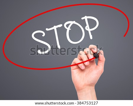 Man Hand writing STOP  with black marker on visual screen. Isolated on background. Business, technology, internet concept. Stock Photo