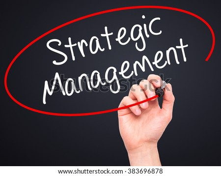 Man Hand writing Strategic Management with black marker on visual screen. Isolated on background. Business, technology, internet concept. Stock Photo